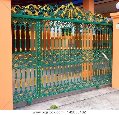 green and gold colored ornamental wrought iron gate on rollers, with peach colored gate posts, Songkhla, Thailand