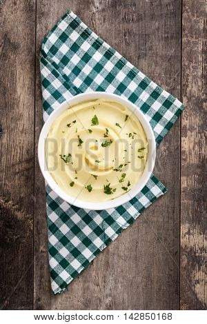 Mashed potato in bowl on rustic wooden background