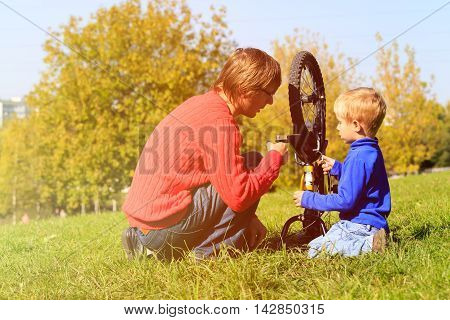 father and son fixing bike in autumn nature