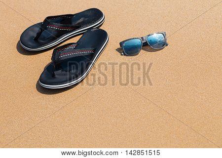 Male thongs and sunglasses lying on the sandy beach; selective focus