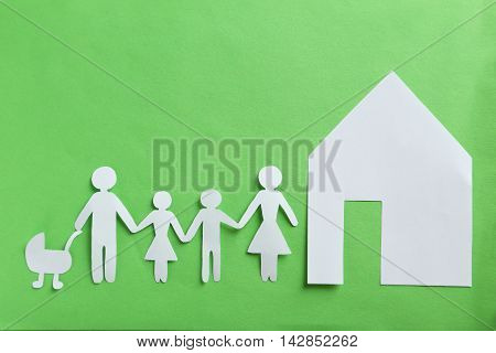 Happy paper family on a green background