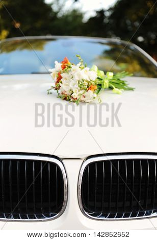Bridal bouquet of flowers on the hood of white cabriolet