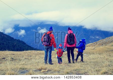 family with little son and daughter hiking in winter mountains