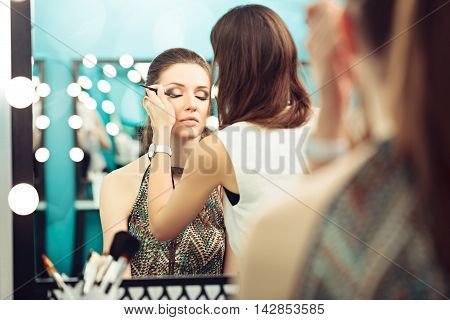 Make-up artist and model at work in front of mirror selective focus on model's reflection