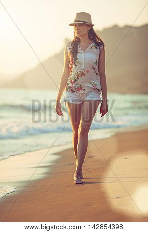 Young beautiful woman walking barefoot along the surf on the sand beach at sunset; lens flares