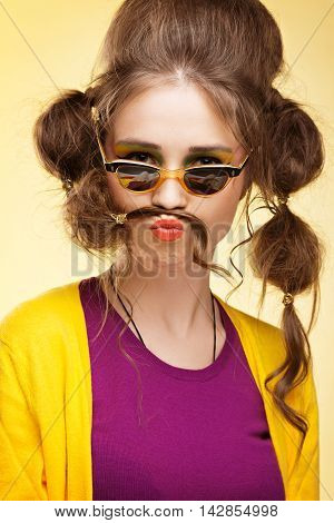 Funny retro girl with mustache made of her hair wearing sunglasses