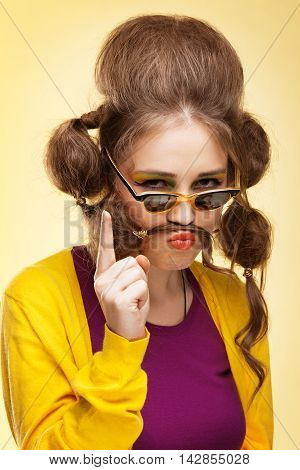 Funny strict girl with mustache made of her hair shaking her finger at camera
