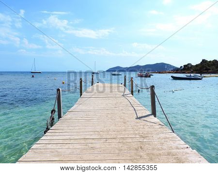 Wooden gangplank or jetty into the sea, with boats and blue sky.