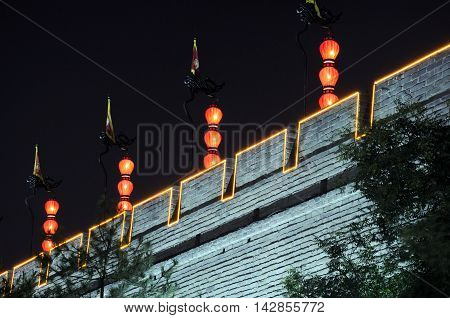 Red lanterns lit up at night and hanging down on top of the Xian city wall in Shaanxi province China.