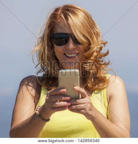 Woman with a blond hair looking at the screen of her phone and smiling. She receiving good news.