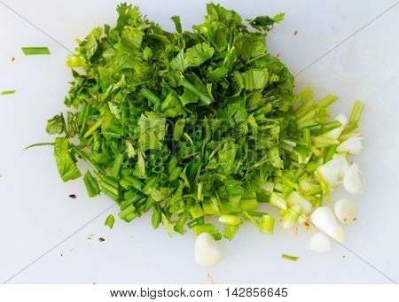 sliced green onions and chopped fresh cilantro on floor