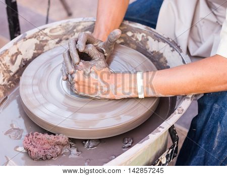 Man hands working with a pottery wheel.
