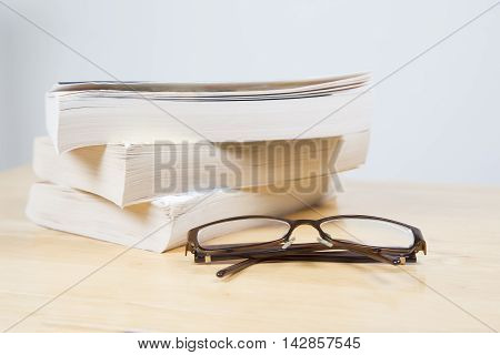 Glasses in front of books on a wooden table