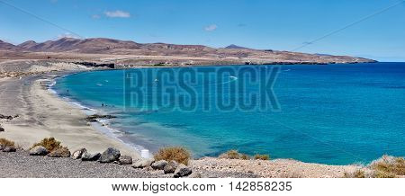 Surfers enjoy wind, sun, blue water, and paradise feeling in a bay of Fuerteventura