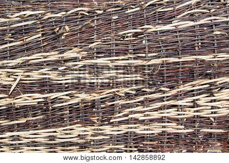 Texture: a part of a fence braided from willow twigs