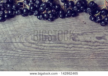 autumn background with black mountain ash berries and copy space over aged wooden desk. vintage toning