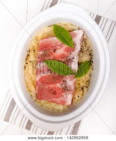 fresh sauerkraut and pork ribs with bay leaf in a white slow cooker