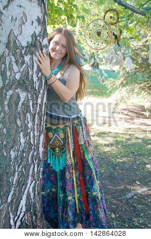 portrait of a girl with fair hair, white, red and turquoise beads, in ethnic clothes in boho style, she stands near the tree and dream catchers