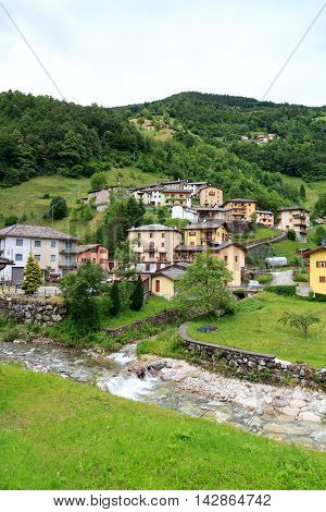 Rava, Italy - June 19, 2016: Panorama of village Rava with river in Lombardy. The village is located in a valley near Bergamo.
