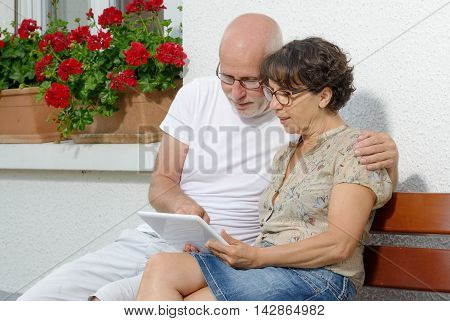 a senior couple with a tablet outside