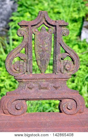 Forged Vintage decorative element of rusty brown metal on a background of green grass.
