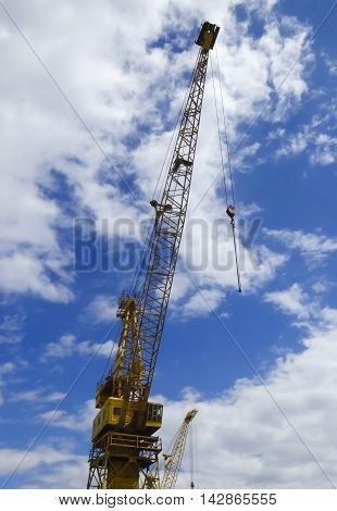 A Towering Yellow Crane Against a Blue Sky with White Clouds