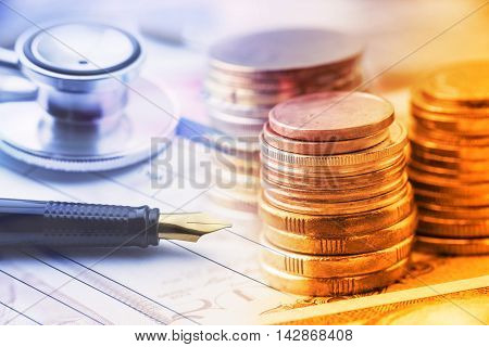 Stack of coins with a fountain pen and an chest-piece of a stethoscope on a table. A concept of healthcare expense which is very expensive due to inflation and the age of a patient older pays higher.
