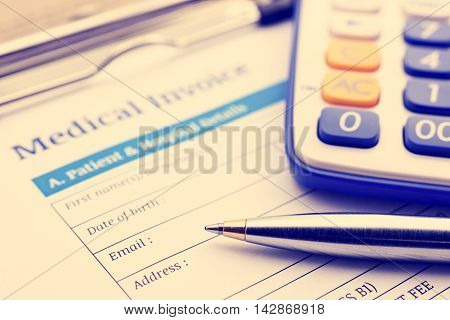 Vintage / retro color style : Blue ballpoint pen a calculator and a medical invoice on a clipboard.