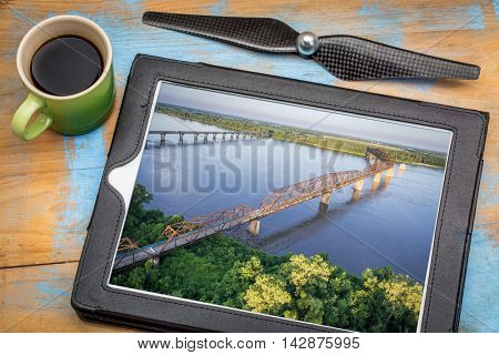 aerial landscape photography concept - reviewing pictures of Chain of Rocks Bridge over Mississippi River on tablet with a drone propeller and coffee