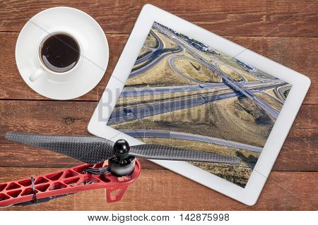 aerial landscape photography concept - reviewing aerial pictures of a freeway in Colorado on a digital tablet with a drone rotor and coffee