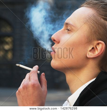 Man smoking against dark background (addiction habit health)