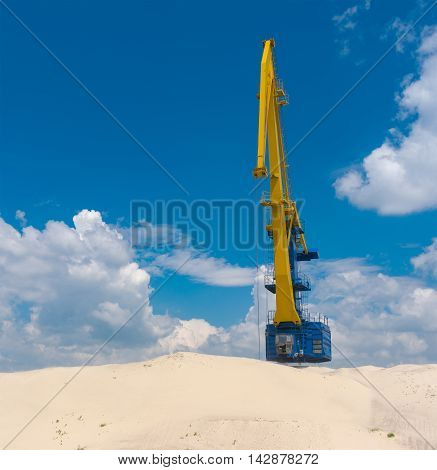 Landscape with big crane blue sky and hills of river sand