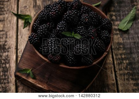 Ripe blackberries in a ceramic bowl on burlap cloth over wooden background close up. Rustic style Selective focus