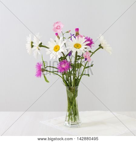 Bouquet of daisies and cornflowers in a glass vase on a white table.