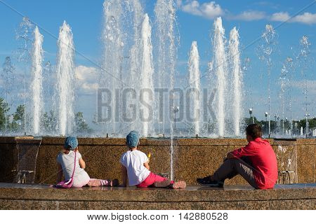 YAROSLAVL, RUSSIA - JULY 10, 2016: Children sit on the parapet and look at the cascade of fountains at the Strelka of the rivers Kotorosl and Volga