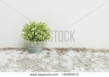 Closeup artificial green plant made from plastic in pot on blurred gray carpet and white cement wall textured background under window light