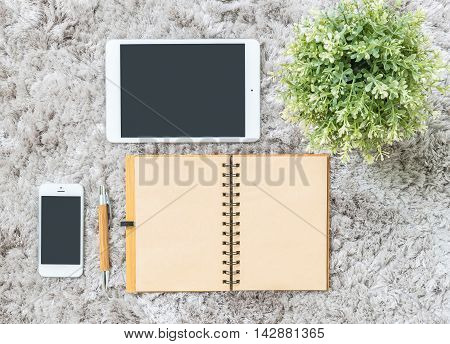 Closeup brown note book brown pen computer notebook tablet phone and artificial plant on gray fabric capet textured background in top view in work concept