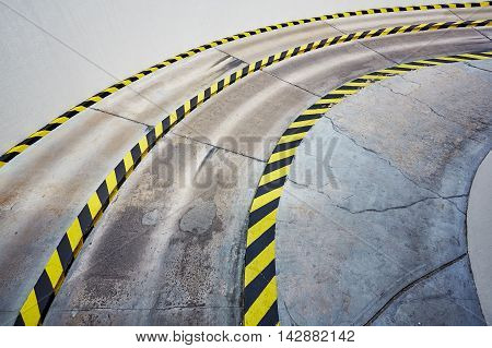 Entry to garage. Empty road to underground car park with black and yellow safety stripes on concrete surface.