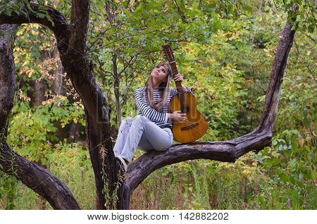 Hippie style girl posing with an acoustic guitar
