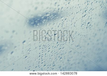 Rain drops on a window glass toned blue, tilt shift