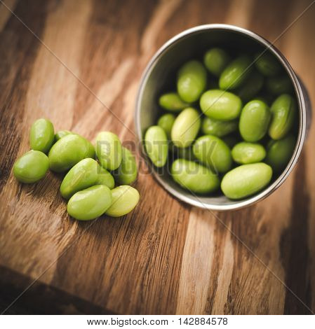 Cooked shelled edamame in a stainless steel container, shallow depth of field