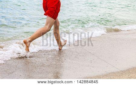 Feet Of Boy Running Along The Beach