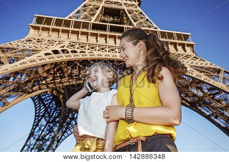 Happy Mother And Daughter Tourists Using Cell Phone. Paris