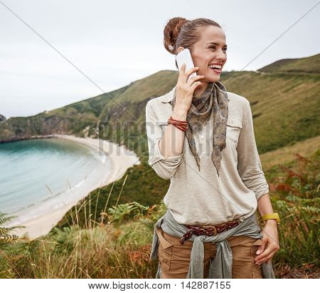 Hiker Looking Aside And Using Mobile Phone In Front Of Ocean