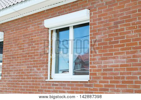 The polymeric window in the house with brick walls
