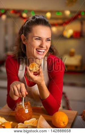 Housewife Tasting Orange Marmalade In Christmas Kitchen