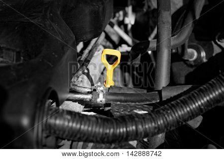 Yellow engine oil dipstick on black motor. Concept for the car service.