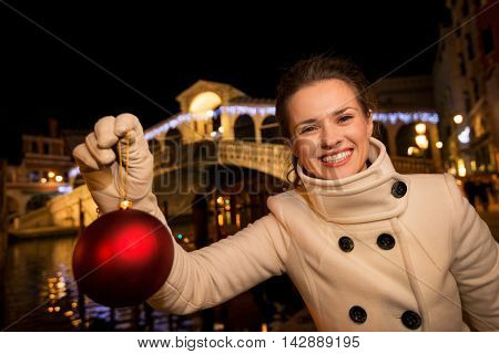 Woman With Christmas Ball Near Rialto Bridge In Venice, Italy