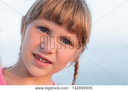 Portrait of tanned baby girl with pigtails closeup