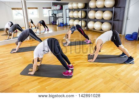 Workout team doing pilates or yoga excerises for flexibility and balance at the fitness gym.